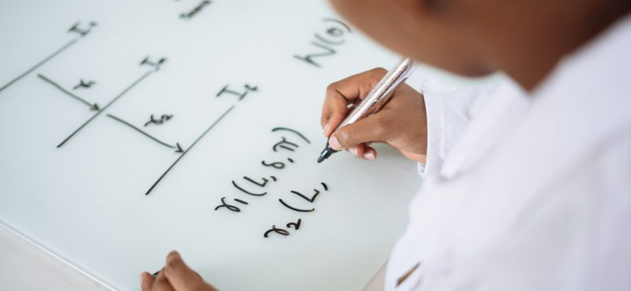 photo of person deriving formula on white board