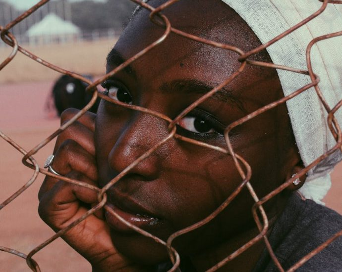 black woman in turban behind wire fence