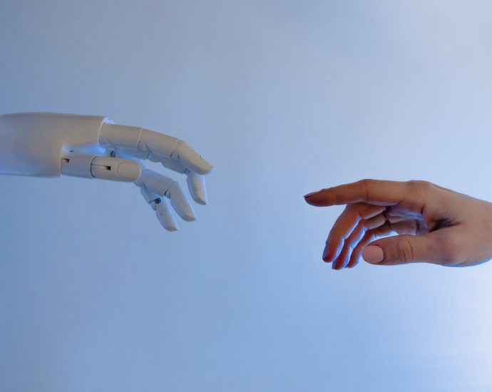 person reaching out to a robot